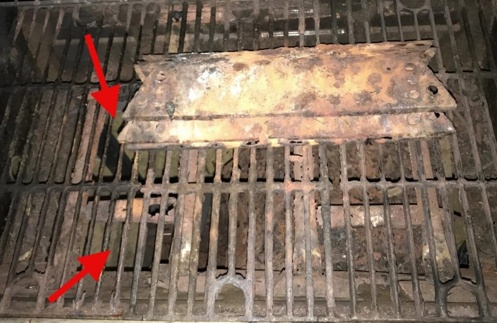 Rusted Out Grill with Grid and Heat Plates Visible. Two red arrows point to a spot in the grill where the grease pan is rusted completely through. There is a hole in the grill.